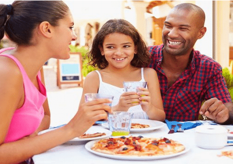family of three eating pizza outside